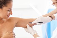 Plastic surgeon making marks on patient`s body royalty free stock photos