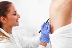 Plastic surgeon making marks on patient`s body stock photo