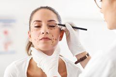 Plastic surgeon making marks on patient`s body stock photos