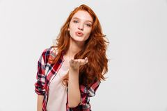Picture of Pleased ginger woman in shirt sends air kiss Royalty Free Stock Photo