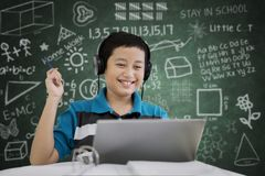 Preteen student studying with a laptop. Picture of preteen student studying with a laptop while listening music in the classroom with scribbles on the chalkboard Royalty Free Stock Photography