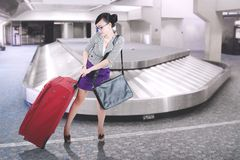 Pretty businesswoman carrying a suitcase at airport. Picture of pretty businesswoman carrying a heavy suitcase while walking near conveyor belt. Shot at airport Royalty Free Stock Images