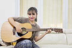 Pretty girl learning to play an acoustic guitar. Picture of pretty girl learning to play an acoustic guitar while sitting in the living room royalty free stock image