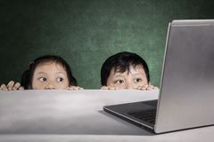 Primary students hiding behind white table. Picture of primary students hiding behind white table while looking a laptop Royalty Free Stock Images