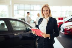 Picture of professional salesperson working in car dealership. Picture of professional female salesperson working in car dealership stock image