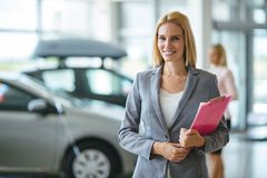Picture of professional salesperson working in car dealership. Picture of professional female salesperson working in car dealership royalty free stock image