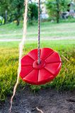 Picture of a red, round swing for kids in the backyard royalty free stock image