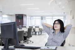 Relaxed businesswoman sitting in the office. Picture of a relaxed businesswoman sitting with a computer and clipboard while daydreaming in the office Royalty Free Stock Photo