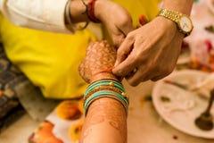 Hindu priest tying a thread on a woman`s hand. stock photos