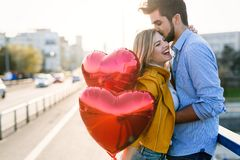 Picture of romantic couple standing outside with baloons. Picture of romantic couple outside with baloons Royalty Free Stock Photo