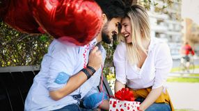 Picture of romantic couple standing outside with baloons. Picture of romantic couple outside with baloons Stock Photos