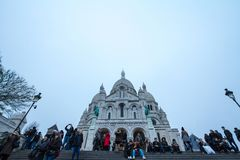 Crowd of tourists in front of Sacre Coeur Basilica in Montmartre, Paris. Picture of the Sacre Coeur basilica of Paris taken during a winter afternoon Royalty Free Stock Images