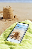 Picture of a sandcastle in a smartphone on the beach Royalty Free Stock Photos