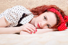 Picture of sensual red haired young woman beautiful pinup girl having fun relaxing lying in bed smiling & looking at camera stock image