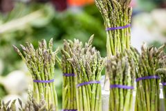 Bundles of green asparagus, cultivated, for sale on a Canadian market in Montreal. Asparagus is a spring vegetable stock images
