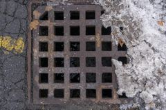 Drainage Pipe during the Winter Thaw. This is a picture of a sewer drain during the winter thaw of spring stock image