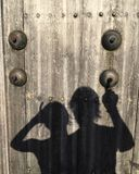 Picture of a the shadow of a women and a man that is ringing on a fake doorbell on a wooden door royalty free stock photos