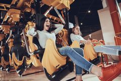 Picture of shocked excited two female friends. Sitting on carousel in amusement park Stock Image