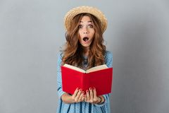 Shocked young pretty woman reading a book. Looking camera. Stock Photo