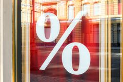Picture of shop window display with percent sign Sale on red poster. Store discount sign in rich luxe vintage style. Seasonal dis royalty free stock photography
