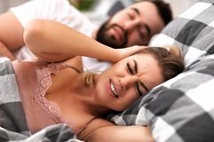 Adult couple suffering from snoring problem in bed Stock Photos