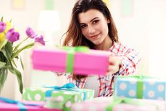 Attractive woman with Easter presents. Picture showing attractive woman preparing Easter presents at home Stock Image