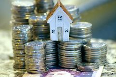 Picture showing the cost of acquiring real property, concept of financing a house, getting a loan... Coins and banknotes royalty free stock photos