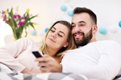 Couple in bed watching TV. Picture showing couple in bed watching TV Stock Photo