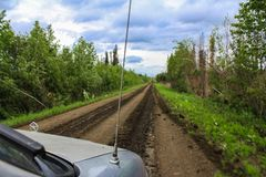 Old grey van driving on a wet dirt road stock photos
