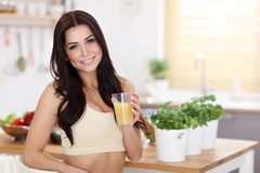 Fit smiling young woman with healthy juice in modern kitchen. Picture showing fit smiling young woman with healthy juice in modern kitchen Royalty Free Stock Images