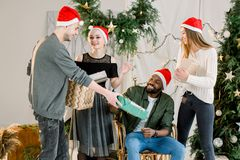 Picture showing group of friends celebrating Christmas at home and exchanging christmas gifts stock photos