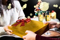 Picture showing group of friends giving and receiving christmas. Gift for friend celebrating Christmas at home and Excited To Open Box Stock Photo