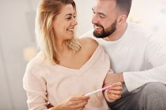 Happy couple with pregnancy test in bedroom. Picture showing happy couple with pregnancy test in bedroom royalty free stock images