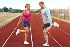 Man and woman racing on outdoor track stock photos