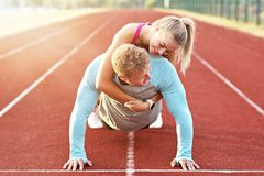 Man and woman racing on outdoor track stock photo