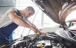 Picture showing muscular car service worker repairing vehicle.  Royalty Free Stock Images