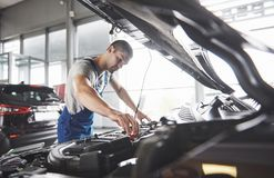 Picture showing muscular car service worker repairing vehicle.  Royalty Free Stock Image