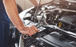 Picture showing muscular car service worker repairing vehicle.  Royalty Free Stock Photos