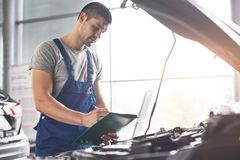 Picture showing muscular car service worker repairing vehicle.  Stock Photos
