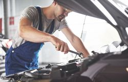 Picture showing muscular car service worker repairing vehicle.  Stock Image