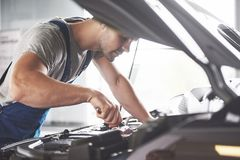 Picture showing muscular car service worker repairing vehicle.  Stock Images