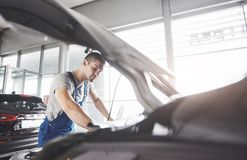 Picture showing muscular car service worker repairing vehicle.  Stock Photo