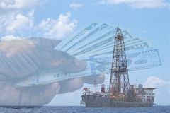 Picture showing oil offshore installation and US dollars in a background. stock photos