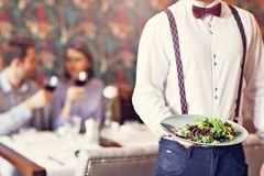 Romantic couple dating in restaurant being served by waiter. Picture showing romantic couple dating in restaurant royalty free stock photos