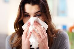 Pretty woman sneezing on tissue on couch in the living-room. Picture showing woman sneezing on tissue on couch in the living-room Royalty Free Stock Image