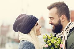 Picture showing young couple with flowers dating in the city stock image