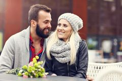 Picture showing young couple with flowers dating in the city. Happy couple with flowers dating in the city royalty free stock image