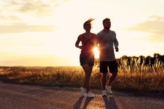 Young couple jogging in the suberbs after sunset royalty free stock photo