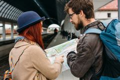Picture showing young couple sightseeing with map. Boyfriend with backpack, red hair girlfriend in blue hat. People holding touris. Picture showing young couple Royalty Free Stock Photography
