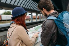 Picture showing young couple sightseeing with map. Boyfriend with backpack, red hair girlfriend in blue hat. People holding touris. Picture showing young couple Stock Photography